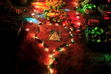 """An image of the Virgin Mary is set on a family altar during the celebration of """"Los Canchules"""" in Nahuizalco November 1, 2015. People remember their deceased relatives and friends during All Saints Day by preparing altars and sharing food with all visitors, prior to the Day Of the Dead. REUTERS/Jose Cabezas"""