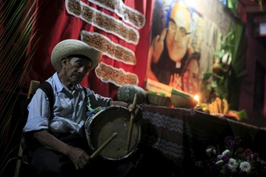 """A man plays the drum at a family altar during the celebration of """"Los Canchules"""" in Nahuizalcoams November 1, 2015. People remember their deceased relatives and friends during All Saints Day by preparing altars and sharing food with all visitors, prior to the Day Of the Dead. REUTERS/Jose Cabezas"""