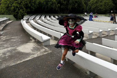 """A girl with her face painted to look like the popular Mexican figure called """"Catrina"""",  jumps as she takes part in the annual Catrina Fest in Mexico City November 1, 2015. According to participants, about 310 women gathered at the Catrina Fest, where women dressed to look like """"Catrina"""", a character also known as """"The Elegant Death"""", created by Guadalupe Posada in the early 1900s. Mexicans celebrate the annual Day of the Dead on November 1 and 2.REUTERS/Carlos Jasso"""