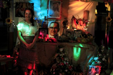 """A girl stands at a family altar during the celebration of """"Los Canchules"""" in Nahuizalco November 1, 2015. People remember their deceased relatives and friends during All Saints Day by preparing altars and sharing food with all visitors, prior to the Day Of the Dead.REUTERS/Jose Cabezas"""