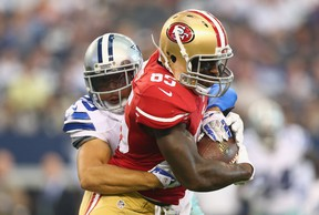 Vernon Davis of the San Francisco 49ers runs the ball against Sterling Moore of the Dallas Cowboys at AT&T Stadium in Arlington on Sept. 7, 2014. (Ronald Martinez/Getty Images/AFP)