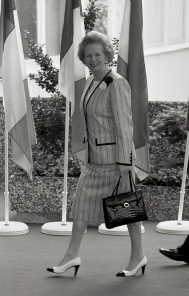 British Prime Minister Margaret Thatcher walks past flags from some of the European nations as she heads toward the second day of meetings during a summit of European community leaders in Hanover, West Germany in this June 28, 1988 file photo.  (REUTERS/Michael Urban/Files)