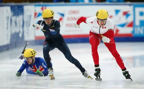 Jack Whelbourne of Britain (left) falls next to Park Se Yeong of South Korea (middle) and Patrick Duffy of Canada as they compete in the men's 1000-metre quarterfinals at the World Short Track Speed Skating Championships in Moscow March 15, 2015. (REUTERS/Maxim Zmeyev)