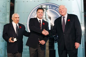 Hockey Hall of Fame inductee Dino Ciccarelli accepts his ring from Chairman of the Hockey Hall of Fame's Board of Directors Jim Gregory (left) and Co-Chairman of Hockey Hall of Fame Selection Committee Bill Hay (right) in Toronto, November 8, 2010. (REUTERS/Mark Blinch)