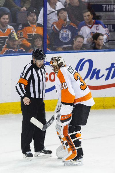 Referee Ian Walsh (left) gives Philadelphia goaltender Michal Neuvirth (30) a delay of game penalty during the second period of a NHL game between the Edmonton Oilers and the Philadelphia Flyers at Rexall Place in Edmonton, Alta. on Tuesday November 3, 2015. Ian Kucerak/Edmonton Sun/Postmedia Network