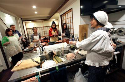 In this Oct. 31, 2015, photo, Shino Fukuyama, right,  hosts a dinner for tourists at her home in Tokyo. Tourists can learn about sushi, kimonos and enjoy dining with locals thanks to EatWith.com, which links travelers to chefs and talented home cooks around the world. (AP Photo/Shuji Kajiyama)