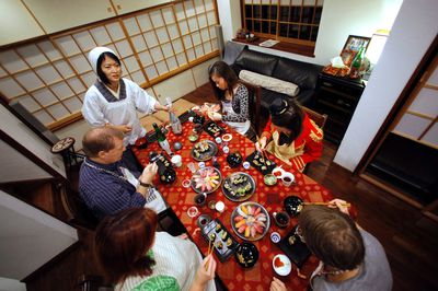 In this Oct. 31, 2015, photo, Shino Fukuyama, standing, teaches U.S. and Swiss tourists how to roll sushi as she hosts a dinner at her home in Tokyo. Tourists can learn about sushi, kimonos and enjoy dining with locals thanks to EatWith.com, which links travelers to chefs and talented home cooks around the world. (AP Photo/Shuji Kajiyama)