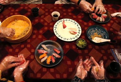 In this Oct. 31, 2015, photo, tourists are taught to make Nigiri sushi with sushi rice, top left, and slices of fish, as they prepare dinner at the home of Shino Fukuyama in Tokyo. Tourists can learn about sushi, kimonos and enjoy dining with locals thanks to EatWith.com, which links travelers to chefs and talented home cooks around the world. (AP Photo/Shuji Kajiyama)