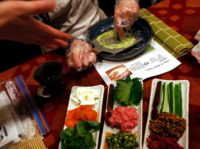 """In this Oct. 31, 2015, photo, a tourist prepares Japanese mustard """"wasabi"""" for a dinner at the home of Shino Fukuyama in Tokyo. Tourists can learn about sushi, kimonos and enjoy dining with locals thanks to EatWith.com, which links travelers to chefs and talented home cooks around the world. (AP Photo/Shuji Kajiyama)"""