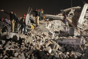 Pakistani volunteers and police officers take part in rescue work following the collapse of a building in Lahore, Pakistan, Wednesday, Nov. 4, 2015. The factory building under construction in an industrial area on the outskirts of Pakistan's eastern city of Lahore collapsed on Wednesday, killing many workers and injuring dozens, officials said. (AP Photo/K.M. Chaudary)