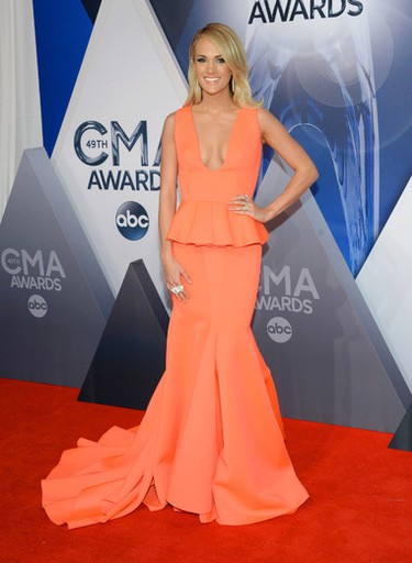 """Carrie Underwood wore a coral peplum stunner from Indian label, Gauri & Nainika. (Photo by Evan Agostini/Invision/AP)  PDRTJS_settings_8272413 = { """"id"""" : """"8272413"""", """"unique_id"""" : """"default"""", """"title"""" : """""""", """"permalink"""" : """""""" }; (function(d,c,j){if(!document.getElementById(j)){var pd=d.createElement(c),s;pd.id=j;pd.src=('https:'==document.location.protocol)?'https://polldaddy.com/js/rating/rating.js':'http://i0.poll.fm/js/rating/rating.js';s=document.getElementsByTagName(c)[0];s.parentNode.insertBefore(pd,s);}}(document,'script','pd-rating-js'));"""