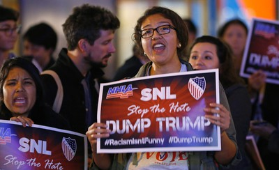 "Protesters opposed to the appearance of Republican presidential candidate Donald Trump's appearance as a guest host on this weekend's ""Saturday Night Live,"" shout anti-Trump slogans as they demonstrate in front of NBC Studios where the show is taped and broadcast, Wednesday, Nov. 4, 2015, in New York. Pressure mounted on NBC to cancel Trump's invitation after a coalition of advocacy groups delivered petitions to the network calling for Trump to be dropped from the show. (AP/Kathy Willens)"