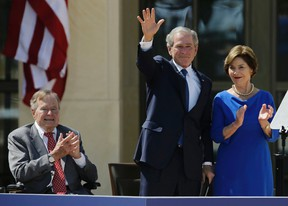 In this April 25, 2013, file photo, Former President George H.W. Bush, left, applauds with Laura Bush after former President George W. Bush's speech during the dedication of the George W. Bush Presidential Center in Dallas. Former President George H.W. Bush is publicly criticizing for the first time key members of his son's administration. A biography of the nation's 41st president to be published in November, 2015, contains his sharply critical assessments of former Vice President Dick Cheney and Defense Secretary Donald Rumsfeld. (AP Photo/David J. Phillip, File)