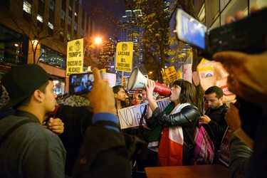 """Karina Garcia, of the ANSWER Coalition, uses a megaphone to lead demonstrators in a chant during a protest against Republican presidential candidate Donald Trump's hosting """"Saturday Night Live"""" in New York, Saturday, Nov. 7, 2015. Despite a 40-year history of lampooning politicians while inviting some to mock themselves as on-air guests, booking a presidential candidate to host the NBC sketch-comedy show is almost unprecedented. (AP Photo/Patrick Sison)"""