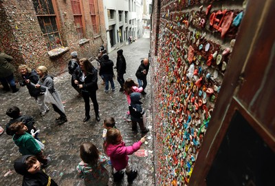 """Visitors check out Seattle's """"gum wall"""" at Pike Place Market, Monday, Nov. 9, 2015. Known as the """"gum wall,"""" the sticky landmark has become a popular attraction to visitors and locals. (AP Photo/Ted S. Warren)"""