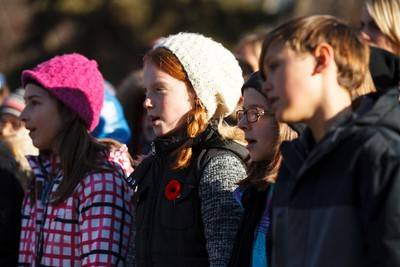 School children sing Oh Canada during No Stone Left Alone at Beechmount Cemetary in Edmonton, Alta., on Tuesday, November 10, 2015. This year marks the 5th annual commemoration ceremonies for the No Stone Left Alone Memorial Foundation. School children from across Canada lay poppies on veterans graves ahead of Remembrance Day. Ian Kucerak/Edmonton Sun/Postmedia Network