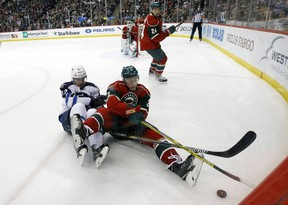 Minnesota Wild center Charlie Coyle (3) and Winnipeg Jets right wing Drew Stafford (12) fall as they chase the puck during the second period of an NHL hockey game in St. Paul, Minn., Tuesday, Nov. 10, 2015. (AP Photo/Ann Heisenfelt)