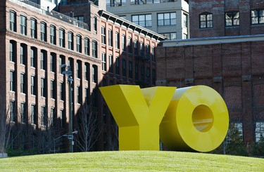 """A bright yellow monumental sculpture by artist Deborah Kass dominates a hill in Brooklyn Bridge Park, Wednesday, Nov. 11, 2015, in New York.  When viewed from Manhattan, the sculpture reads """"Yo,"""" but when viewed from Brooklyn it spells the popular Yiddish expression """"Oy.""""  The aluminum sculpture was commissioned by Brooklyn developer Two Trees Management Company and will remain up until August 2016. (AP Photo/Kathy Willens)"""