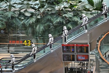 Imperial Stormtroopers from the Star Wars film franchise travel down an escalator during a promotional event at the Changi International airport in Singapore on November 12, 2015. A promotional event for the Star Wars film franchise was held at Singapore's Changi airport as part of the arrival of an All Nippon Airways (ANA) Boeing 787 aircraft painted in special Star Wars livery in the likeness of popular robot character R2-D2. AFP PHOTO / ROSLAN RAHMAN