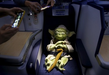 Visitors take photos of a Yoda plush toy sitting in the business class section during a tour of the Star Wars themed All Nippon Airways ANA R2D2 Boeing 787 Dreamliner aircraft at Singapore's Changi Airport November 12, 2015. The aircraft was opened to the media on Thursday as it makes its first Asian stop outside Japan. REUTERS/Edgar Su