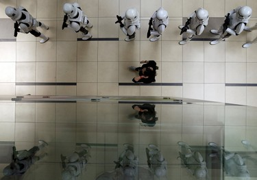 """A coordinator checks on Stormtroopers lining up before they perform for members of the public at a life-sized """"Star Wars"""" X-wing Fighter model on display at Singapore's Changi Airport November 12, 2015. The event coincides with a media tour of a """"Star Wars""""-themed All Nippon Airways ANA R2-D2 Boeing 787 Dreamliner aircraft on Thursday as it makes its first Asian stop outside Japan.   REUTERS/Edgar Su"""