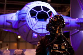 """An actor dressed as a TIE figther pilot poses by a giant model of a Star Wars' TIE fighter for the presentation of US game developer, publisher and distributor Electronic Arts (EA)'s """"Star Wars Battlefront"""", during the Madrid Games Week 2015 in Madrid on October 1, 2015. The video game fair is open from October 1 to 4.  AFP PHOTO/ SEBASTIEN BERDA"""