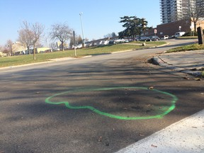 Green spray paint at the corner of Golden Orchard Dr. and Grand Forks Rd., in Mississauga, marks the spot where a man, 26, was shot by Peel Regional Police early Saturday. (CHRIS DOUCETTE, Toronto Sun)