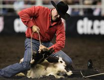 Scot Meeks (Clyde, TX) takes part in the Tie-down Roping event during day one of the Canadian Finals Rodeo at Rexall Place, in Edmonton, Alta. on Wednesday Nov. 11, 2015. David Bloom/Edmonton Sun/Postmedia Network