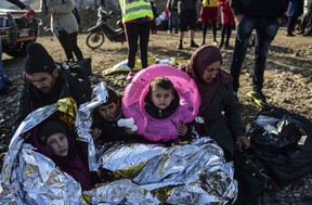 A Syrian family waits after arriving on the Greek island of Lesbos along with other migrants and refugees, on November 17, 2015, after crossing the Aegean Sea from Turkey. (AFP PHOTO/BULENT KILIC)