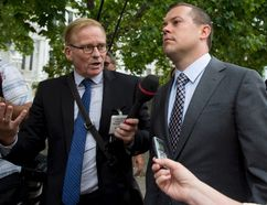 Chris Woodcock, former director of issues management in the Prime Minister's Office, is scrummed by reporters, including CTV's Robert Fife, who broke the story on the Duffy senate expenses scandal, as he leaves the courthouse in Ottawa following his second day of testimony at the trial of Sen. Mike Duffy, a former Conservative caucus member, on Tuesday, Aug. 25, 2015. THE CANADIAN PRESS/Justin Tang