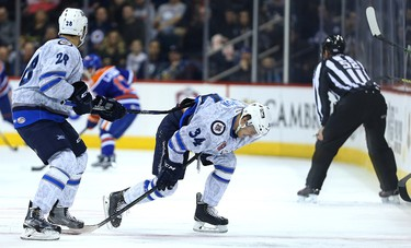 Manitoba Moose forward JC Lipon (right) is given a push toward the bench by captain Patrice Cormier after blocking a shot against the Bakersfield Condors during AHL action in Winnipeg on Fri., Nov. 20, 2015. Kevin King/Winnipeg Sun/Postmedia Network
