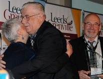 Athens' construction mogul George Tackaberry shares a hug with Marlene Thake, widow of Westport politician Bill Thake, after Tackaberry was named winner of the Bill Thake Memorial Economic Development Leadership Award, seen in the hands of United Counties Warden David Gordon.