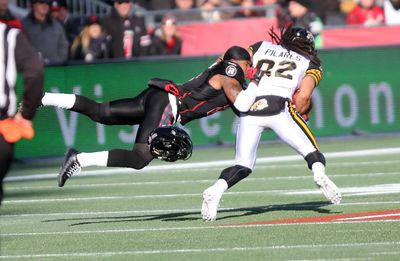 Ottawa RedBlacks defensive back Jovon Johnson loses his helmet as he tackles Kealoha Pilares of the Hamilton Tiger-Cats in the CFL East Final at TD Place on Sunday, Nov. 22, 2015. (Chris Hofley/Ottawa Sun)
