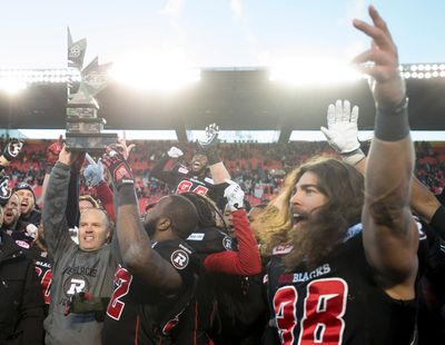 Ottawa Redblacks head coach Rick Campbell holds up the East Division trophy as players celebrate following their win over the Hamilton Tiger-Cats in the CFL East final Sunday, November 22, 2015 in Ottawa. The Redblacks will advance to the Grey Cup after defeating the Hamilton Tiger-Cats. THE CANADIAN PRESS/Adrian Wyld