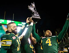 Eskimos QB Mike Reilly, left, and slotback Adarius Bowman hoist the west division championship trophy after defeating the Stampeders 45-31 at Commonwealth Stadium on Sunday. (Codie McLachlan, Edmonton Sun)