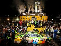 Kyle Busch, driver of the #18 M&M's Crispy Toyota, celebrates with the trophy in Victory Lane after winning the series championship and the NASCAR Sprint Cup Series Ford EcoBoost 400 at Homestead-Miami Speedway on November 22, 2015 in Homestead, Florida.