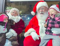 Annie Alexander, 2, gives a shriek of excitement from Santa's knee as her sister, Juniper, 6 months, looks on from the lap of Mrs. Claus. (Darryl Coote/Kincardine News)