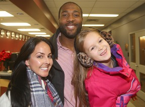 Edmonton Eskimos offensive lineman Chris Greaves (c) walks through the air terminal with his fiancee Elizabeth Aquin (l) and her daughter Isabelle upon his arrival in Winnipeg, Man. Tuesday November 24, 2015 for the Grey Cup. Brian Donogh/Winnipeg Sun/Postmedia Network