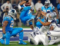 Panthers quarterback Cam Newton is upended and lands in the end zone for a touchdown against the Cowboys during second half NFL action in Arlington, Texas on Thursday, Nov. 26, 2015. (AP Photo/Brandon Wade)