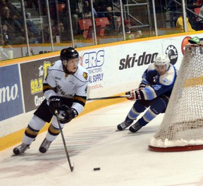 London defenseman Olli Juolevi (left) cuts around his net while the Owen Sound Attack's Kevin Hancock tries to put the hook on him during the Knights 4-1 win on Saturday in Ontario Hockey League action.