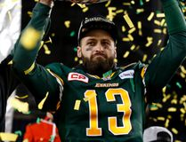 Edmonton Eskimos quarterback Mike Reilly lifts the Grey Cup over his head as he celebrates beating the Ottawa REDBLACKS in the CFL's 103rd Grey Cup football championship at Investors Group Field in Winnipeg, Man., Sunday November 29, 2015. Al Charest/Calgary Sun/Postmedia Network