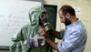 This image made from an AP video posted on Sept. 18, 2013, shows a volunteer adjusting a students gas mask and protective suit during a session on reacting to a chemical weapons attack, in Aleppo, Syria. (AP Photo via AP video, File)