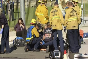Rescue crews tend to the injured in the intersection outside the Inland Regional Center in San Bernardino, California in this still image taken from video December 2, 2015. At least 20 people were reported injured in an active shooter situation, according to news reports.  REUTERS/NBCLA.com/Handout via Reuters