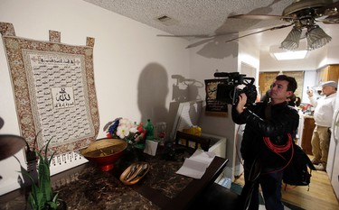 A member of the media films a wall tapestry displaying religous writing in the living room of an apartment in Redlands, Calif., shared by San Bernardino shooting rampage suspects Syed Farook and his wife, Tashfeen Malik, Friday, Dec. 4, 2015, after the building landlord invited media into the townhouse rented by the California attackers. (AP Photo/Chris Carlson)