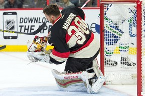 Ottawa Senators goalie Andrew Hammond (30) loses his helmet following a shot on goal in the second period against the Vancouver Canucks at Canadian Tire Centre. Mandatory Credit: Marc DesRosiers-USA TODAY Sports