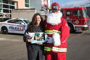 Marisa Thorburn of the London police department?s victim services unit and Randy Evans of the London fire department encourage citizens to participate in their Christmas toy drive Saturday. (DEREK RUTTAN, The London Free Press)