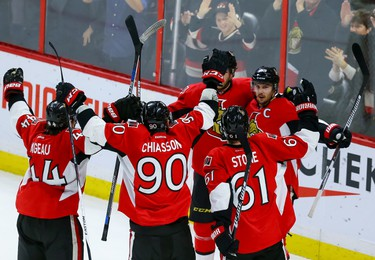 Ottawa Senators captain Erik Karlsson (65) is congratulated by his teammates after scoring the game winning overtime goal against the against the New York Islanders during NHL action in Ottawa, Ont. on Saturday December 5, 2015. Errol McGihon/Ottawa Sun/Postmedia Network