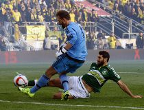 Portland Timbers midfielder Diego Valeri, right, of Argentina, scores a goal against Columbus Crew goalkeeper Steve Clark during the first half of the MLS Cup championship soccer game Sunday, Dec. 6, 2015, in Columbus, Ohio. (AP Photo/Paul Vernon)
