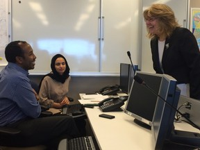 Immigration minister Erna Braun talks with workers inside the province's co-ordination centre for refugee settlement on Tuesday.