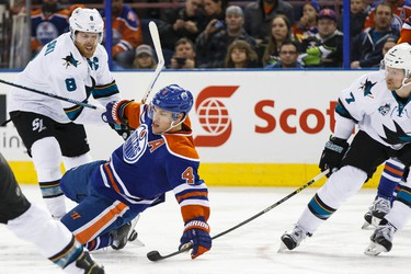 Edmonton forward Taylor Hall (4) is taken down by San Jose centre Joe Pavelski (8) and defenceman Paul Martin (7) during the third period of a NHL game between the Edmonton Oilers and the San Jose Sharks at Rexall Place in Edmonton, Alta. on Wednesday December 9, 2015. Ian Kucerak/Edmonton Sun/Postmedia Network
